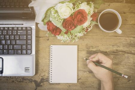 letter writing: Note book paper on wooden background,Blank note book ,Laptop and cup of coffee,roses with hand working on old wooden table, valentine,business,relax,home office concept,Vintage tone,selective focus. Stock Photo