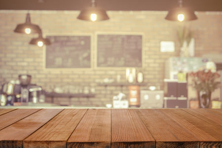 Empty brown wooden table and Coffee shop interior with some people meeting blur background with bokeh image, for product display montage,can be used for montage or display your products Zdjęcie Seryjne