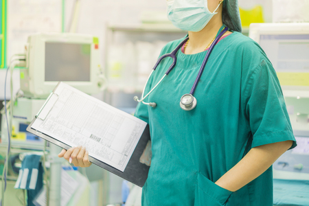 female doctor with stethoscope on hospital corridor holding clipboard  with an operating room at the background ,Healthcare and medical concept,selective focus. Imagens