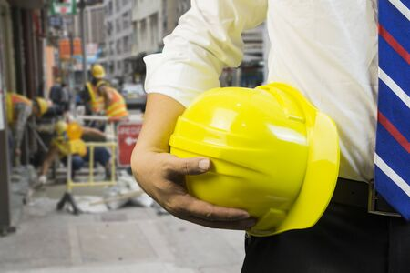 indenture: Businessman with construction yellow helmet,engineer or worker hold in hand yellow helmet for workers security  in front of construction blur background ,selective focus,vintage tone