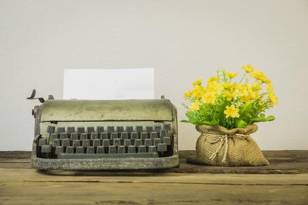 白い背景に、木の板、ヴィンテージ タイプライターや紙、ビンテージ トーン、選択と集中の空白のシート上に配置レトロ タイプライターのテーブ