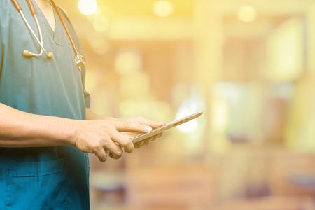 Männliche Arzt, Medizinstudenten oder Chirurg mit digitalen Tablet und Laptop während der Konferenz, Fähigkeit überprüfen mit digitalen Systemunterstützung für Patienten, Testergebnisse und Patientenregistrierung, selektiven Fokus Standard-Bild