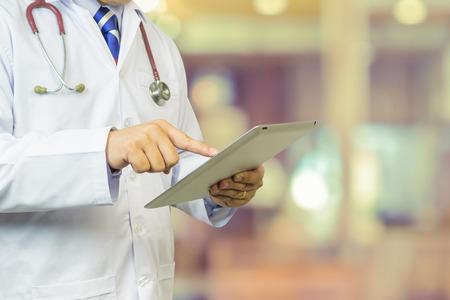 cirujano: Doctor de sexo masculino, estudiantes de medicina o cirujano que usa la tableta digital y port�til durante la conferencia, de Salud, con el apoyo del sistema digital para el paciente, los resultados de las pruebas y el registro de pacientes, el color de la vendimia