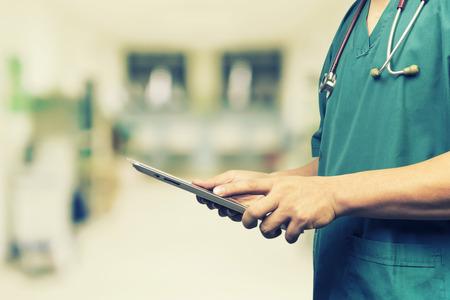 Männliche Arzt, Medizinstudenten oder Chirurg mit digitalen Tablet und Laptop während der Konferenz, Health Check mit digitalen Systemunterstützung für Patienten, Testergebnisse und Patientenregistrierung, Jahrgang Farbe