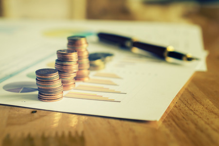 Saving money concept,graph, stacks of coins ,chart and pen ,copy space.selective focus,vintage color Imagens
