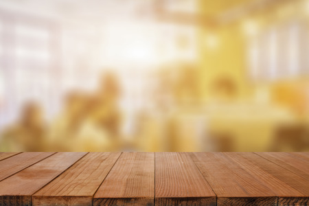 Empty brown wooden table and Coffee shop interior with some people meeting blur background with bokeh image, for product display montage,can be used for montage or display your products Stock Photo
