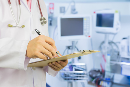 personal data assistant: male doctor with stethoscope on hospital corridor holding clipboard and writing a prescription,Doctor,Medical Exam.,Healthcare and medical concept,test results ,patient registration,selective focus. Stock Photo