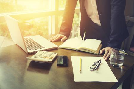 vista lateral del hombre de negocios que trabaja en la oficina con ordenador portátil y documentos en su escritorio en su oficina mientras mira consultor grave, el concepto de abogado, luz de la mañana, el color de la vendimia, foco selectivo Foto de archivo
