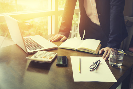 Vue de côté de l'homme d'affaires travaillant au bureau avec un ordinateur portable et des documents sur son bureau à son bureau en regardant un consultant sérieux, concept d'avocat, lumière du matin, couleur vintage, orientation sélective Banque d'images