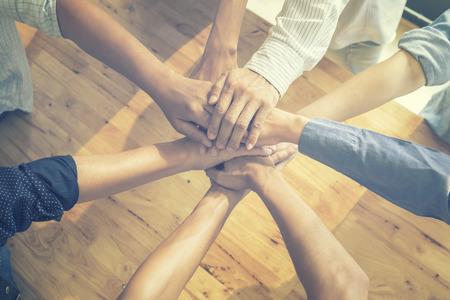 Travail d'équipe, équipe des activités debout les mains ensemble dans le bureau. Les gens d'affaires joignant les mains ensemble. Les mains d'équipe les gens ensemble, travail d'équipe en ligne. Travail d'équipe, joindre les mains ensemble, couleur vintage