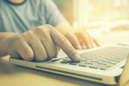 business,hand of start up business man working document and laptop in office.hands with laptop in pressing enter button,copy space,vintage color,selective focus Banque d'images