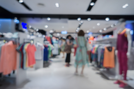 blurred abstract background of multicolored cotton clothing on the shelves of fashion shop and city shopping people crowd at marketplace shoe shop abstract background.vintage color