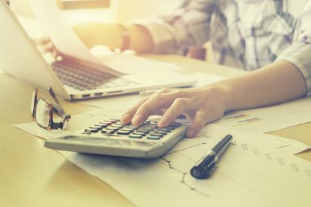 電卓ノート パソコンで投資チャート分析の実業家。会計とオフィスの技術。事務所、分析 plans.selective フォーカス、ヴィンテージ色でノート パソコ 写真素材