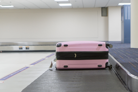 conveyor belt: Baggage claim at the airport,suitcases on a luggage band on the airport,Baggage on conveyor belt at the airport - selective focus,vintage color