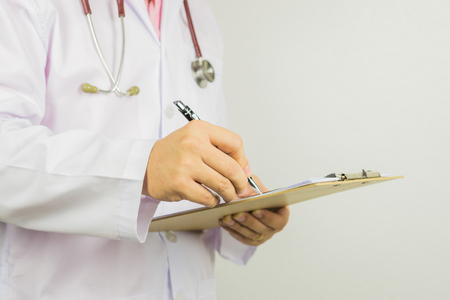 male doctor with stethoscope on hospital corridor holding clipboard and writing a prescription,Doctor,Medical Exam.,Healthcare and medical concept,test results ,patient registration,selective focus. Stock Photo