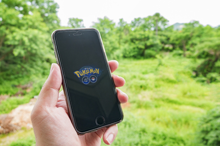 Bangkok, Thailand - July 17, 2016 : Apple iPhone6s held in one hand showing its screen with   application Pokemon GO shows a Pokemon encounter overlain on the real world