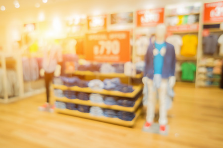 Blur or Defocus image of jeans display in the fashion store,luxury and fashionable brand, Jeans shirts at shelf in shop, with bokeh for use as Background,vintage retro color