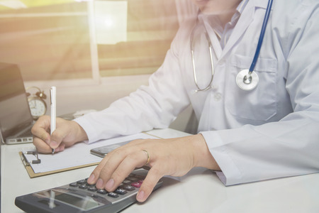 health care provider: young medical doctor caucasian healthcare professional wearing a white coat with stethoscope in hospital ,doctors office calculates on an electronic calculator,selective focus,vintage color Stock Photo