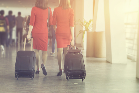 air hostes, women pulling suitcase in modern airport terminal. Travelling  wearing red style clothes walking away with his luggage while waiting for transport.selective focus,vintage color Archivio Fotografico