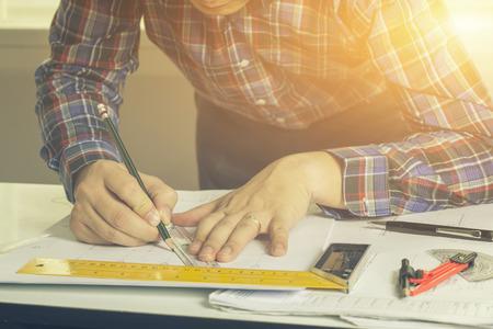 architetto attingendo architettonico Proiezione con la matita sui disegni urbani. la casa, i piani architettonici di costruzione, matita e righello sulla scrivania, messa a fuoco selettiva, colore d'epoca