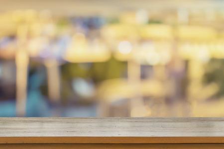 茶色の木製のテーブルを空にレストラン ライトの背景をぼかし、モンタージュのため使用することができますか、あなたの製品を表示 写真素材
