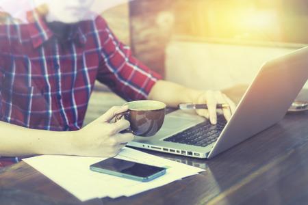 opstarten met behulp van tablet-computer-net boek en het drinken van koffie  thee in een coffeeshop, het werken met de laptop tijdens een koffiepauze, tijdens het werken op zijn laptop pc in een cafe, selectieve aandacht, vintage kleur