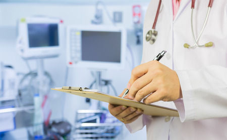 prescript: male doctor with stethoscope on hospital corridor holding clipboard and writing a prescription,Doctor,Medical Exam.,Healthcare and medical concept,test results ,patient registration,selective focus. Stock Photo