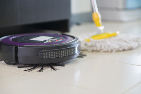 floor washing robot VS traditional mop on laminate floor,selective focus Stock Photo