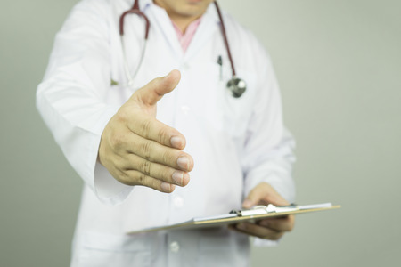 labcoat: Handshake Gesture from Doctor with stethoscope on white background. success smart medical working in hospital,selective focus.vintage color.healhcare and medical concept