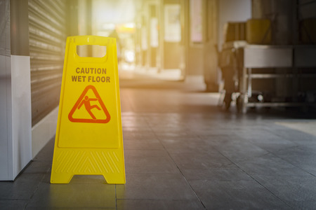 Sign showing warning of caution wet floor,selective focus,vintage color. Stock Photo