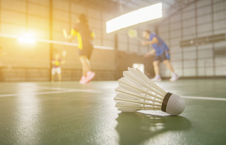 A set of badminton concept.Badminton ball (shuttlecock) and racket on court floor,Paddle ,the shuttlecock and badminton courts with players competing in modern gym,selective focus,vintage color