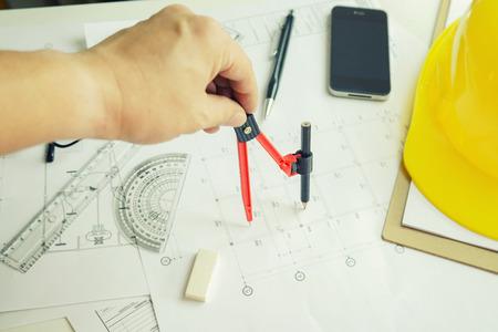 建築家建築プロジェクトに図面の手都市の図面を鉛筆で投影します。家の青写真を計画、建築計画デザイン ホーム、机、セレクティブ フォーカス、