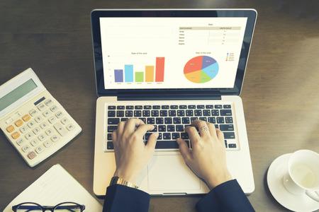 Mujer de negocios de utilizar la computadora portátil en línea para el análisis de la carta financiera, la escritura de plan de negocios, abrir net-book, teléfono, tabletas, con espacio de copia de la pantalla, luz de la mañana, color vintage Foto de archivo - 62835709
