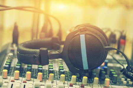 音と光のミキサー コンソール、トップ、ブティック録音スタジオ コントロール デスク、選択と集中、ヴィンテージ色で休んでヘッドフォンでサウ 写真素材