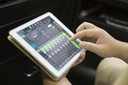 スタジオの音と光のミキサー コンソールでの作業手サウンド エンジニア錠デジタル ミキサーとサウンド ミキサー オーディオ ミキサーの音量を調 写真素材
