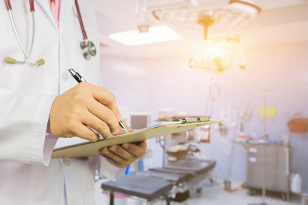 personal data assistant: Male Doctor with files and stethoscope on hospital corridor holding clipboard and writing a prescription,Doctor,Medical Exam.,Healthcare and medical concept,test results, registration,selective focus.