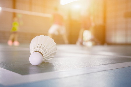 A set of badminton concept.Badminton ball (shuttlecock) and racket on court floor,Paddle ,the shuttlecock and badminton courts with players competing in modern gym,selective focus,vintage color Stock Photo