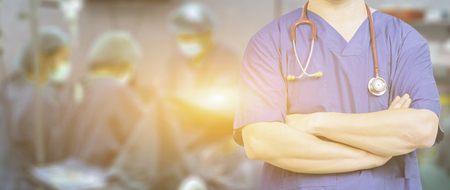 medical technical equipment: Medical Doctor surgeon posing with arms crossed in an operating theatre,surgical room,doctor with operating room,healthcare and medical concept,stethoscope,healtcare ,background banner Stock Photo
