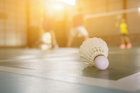 shuttlecock: A set of badminton concept.Badminton ball (shuttlecock) and racket on court floor,Paddle ,the shuttlecock and badminton courts with players competing in modern gym,selective focus,vintage color Stock Photo