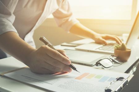 Business-Mann arbeitet im Büro mit Laptop und Dokumente auf seinem Schreibtisch, Berater Anwalt Konzept, junge männliche Schüler schreiben und schreiben auf Business-Diagramm sitzen am Holztisch, Vintage-Farbe