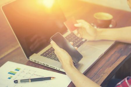 Mann überprüft Kontostand auf dem Smartphone mit Mobile Banking application.Online Zahlung, die Hände der Männer mit einer Kreditkarte und Smartphone für Online-Shopping, selektiver Fokus, Jahrgang Farbe