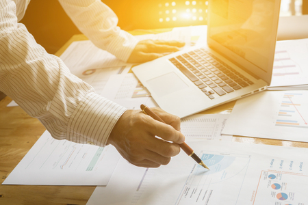 person writing: Person pointing writing goals on a paper,writing business plan at workplace,man holding pens and papers, making notes in documents, on the table in office,vintage color,morning light ,selective focus. Stock Photo