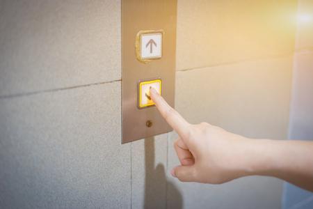 Mujeres empresarias presionando el botón del ascensor. el dedo presiona el botón del elevador. Botón rojo. ascensor. Piso alto. Se acerca el botón de la llamada del ascensor. Tocando el panel de control del ascensor Foto de archivo - 66428336