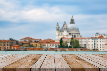 italy background: Wood table top on Blurred background of Grand Canal and Basilica Santa Maria della Salute, Venice, Italy and sunny day,Italy Europe.vintage tone color,can be used display your products