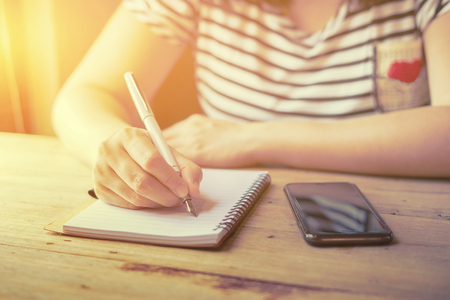 Young female student writes information from portable net-book while prepare for lectures in University campus,hipster  working on phone while sitting in cafe,female hands with pen writing on notebook