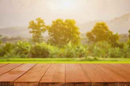 leer dunklen Schreibtisch Tisch und Grasfläche von grünen Wald und Sonnenuntergang grünen Hintergrund Garten Bokeh für eine Gastronomie oder Lebensmittel verschwommen, mit Bokeh Bild kann für die Montage oder zeigen Sie Ihre Produkte verwendet werden,