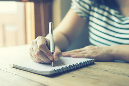 female hands with pen writing on notebook on wooden table ,young girl writing into her diary, in the park,Woman writing recipient address on mailing envelope,female hands sending letter,vintage color
