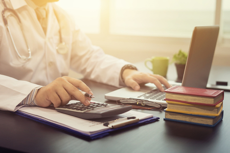 Giovane medico indoeuropeo professionista sanitario indossando un camice bianco con stetoscopio in ospedale, ufficio del medico calcola su un calcolatore elettronico, messa a fuoco selettiva, colore vintage Archivio Fotografico - 66428223