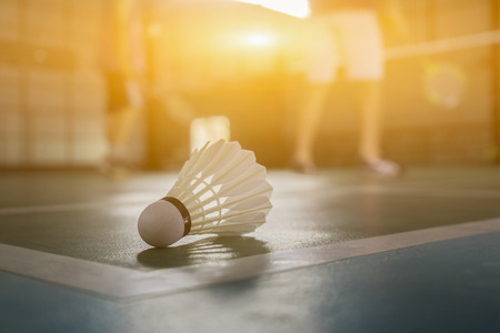 A set of badminton concept.Badminton ball (shuttlecock) and racket on court floor,Paddle ,the shuttlecock and badminton courts with players competing in modern gym,selective focus,vintage color Stockfoto