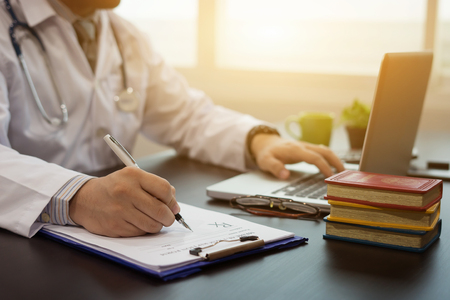 writing doctor,surgeon,nurse,pharmacy with stethoscope on hospital and,writing a prescription, medical prescription in surgery at desk,medicine, pharmaceutics, health care and people concept,